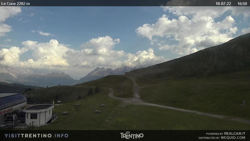 Webcam Moena - Alpe Lusia - Le Cune - Altitude: 2,210 metresArea: Le CunePanoramic viewpoint: static webcam. Valbona-Le Cune cabin lift arrival (second trunk). In the background, Cima Lastè, the group Pale di San Martino, the Lagorai mountain chain. The slopes